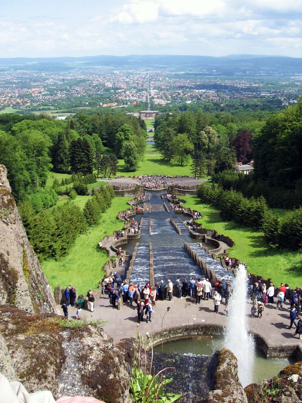 "View from the Bergpark Wilhelmshöhe (mountain park) to Kassel, with the Baroque Water feature in operation. In background the castle Wilhelmshöhe and street ""Wilhelmshöher Allee"" to city. Wikimedia Commons."