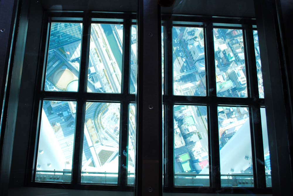 Looking down through the glass floor to the streets far below.